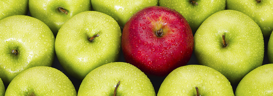group of green apples with one juicy red one
